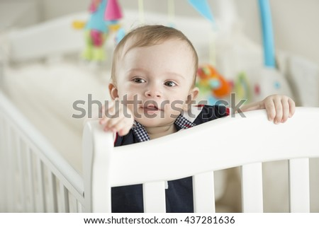 Portrait of 9 month old boy teething and posing in white cradle - stock photo