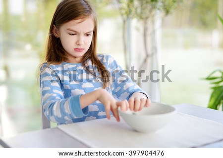 Portrait of moody young girl sitting at breakfast table - stock photo