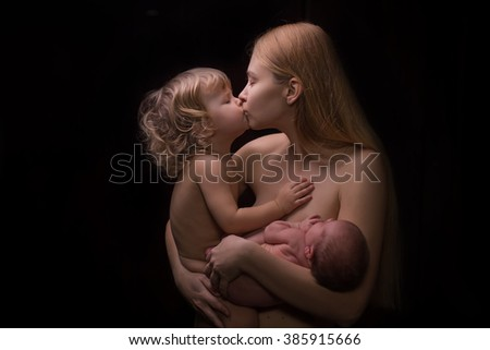 portrait of mother and babies nude on black background symbol of love family - stock photo