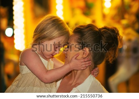 Portrait of mother and baby girl hugging in front of carousel - stock photo