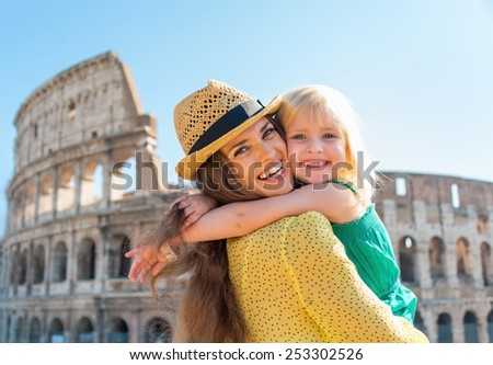 Portrait of mother and baby girl hugging in front of colosseum in rome, italy - stock photo