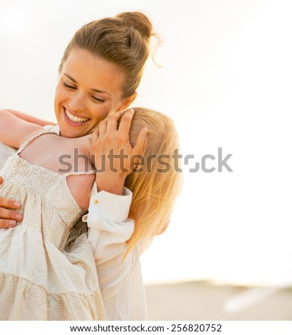 Portrait of mother and baby girl hugging on beach at the evening - stock photo