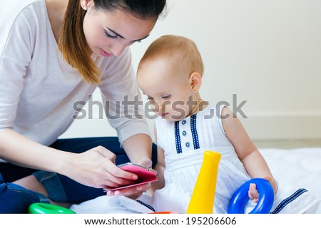 Portrait of Mother and baby girl using a smartphone at home  - stock photo