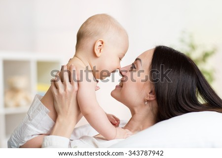 Portrait of mother and baby laugh and play lying on bed - stock photo