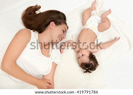 portrait of mother and baby lie on white - stock photo