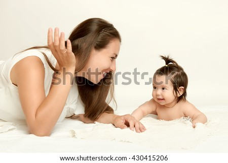portrait of mother and baby lie on white towel - stock photo