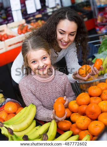 Portrait of mother and child purchasing sweet tangerines in supermarket . Focus on girl