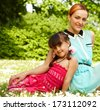 Portrait of mother and child sitting on the grass enjoying sun - stock photo
