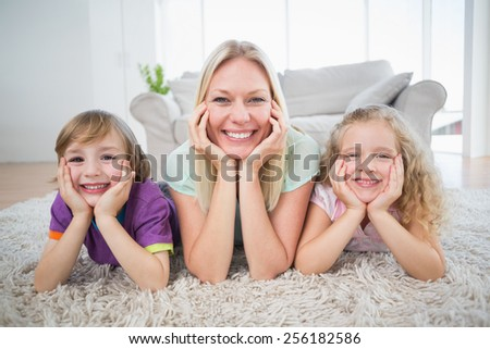 Portrait of mother and children with head in hands lying on rug at home - stock photo