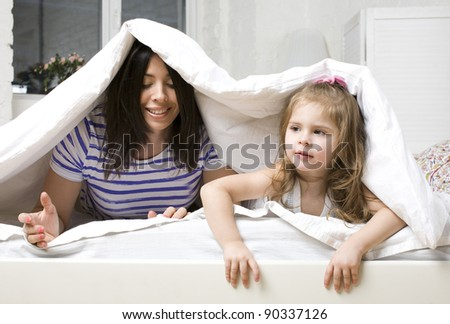 portrait of mother and daughter laying in bed - stock photo