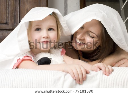 Portrait of mother and daughter laying in bed hugging and smiling