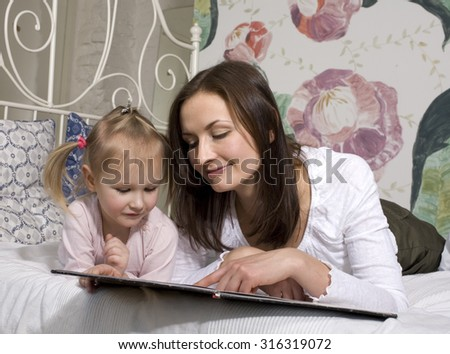 portrait of mother and daughter laying in bed reading book smiling - stock photo