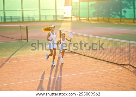 portrait of mother and daughter on the tennis court