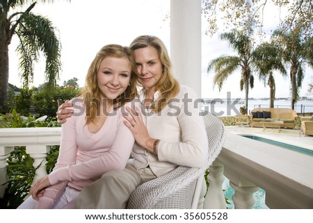 Portrait of mother and daughter on waterfront terrace - stock photo