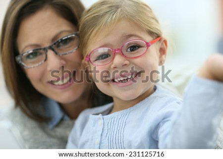 Portrait of mother and daughter wearing eyeglasses - stock photo
