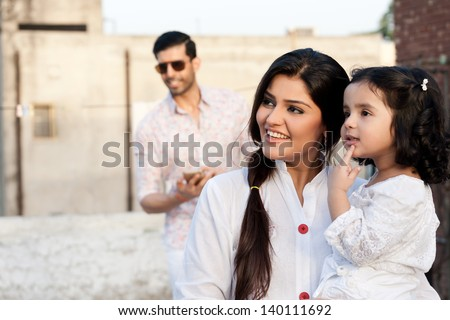 portrait of mother and daughter with the father in background - stock photo