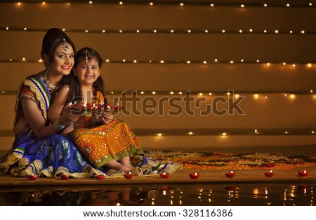 Portrait of mother and daughter with tray of diyas - stock photo