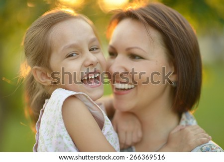 Portrait of mother and her daughter outdoors at sunset - stock photo