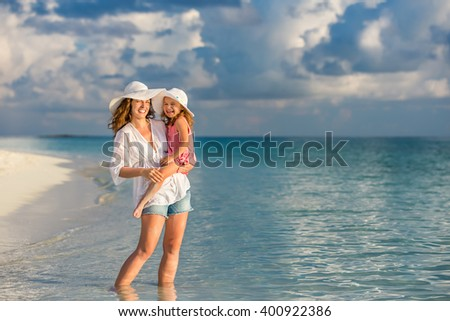 Portrait of mother and little daughter on the beach - stock photo