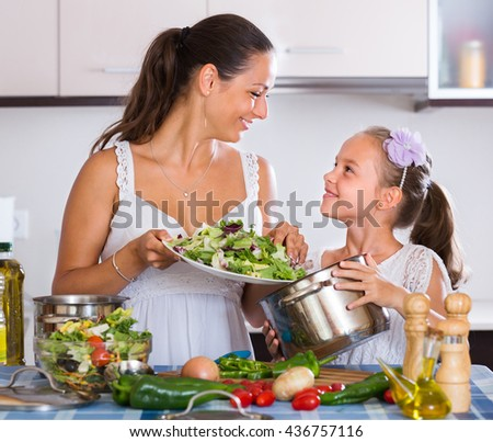 Portrait of mother and little girl cooking vegetables