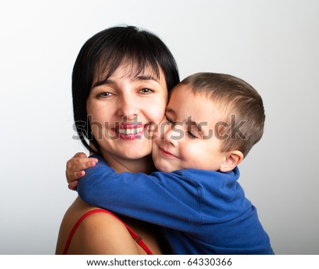 Portrait of mother and son embrace on grey gradient background - stock photo