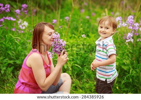 Portrait of mother and son together sitting in on flower meadow field  in countryside village, smiling, holding and smelling flowers, happy family concept, summer fun activity, mothers day holiday - stock photo