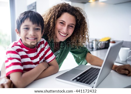Portrait of mother and son using laptop in kitchen at home - stock photo