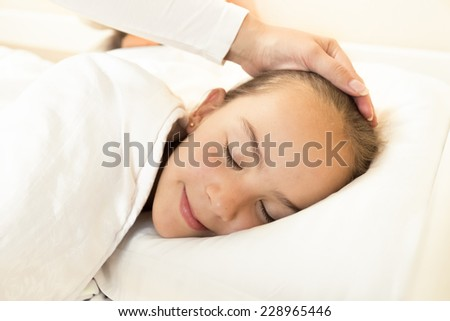 Portrait of mother hand caressing sleeping daughter on hand