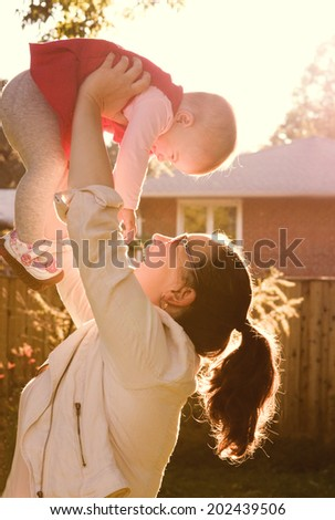 Portrait of mother holding her child on her hands very high against sunlight on sunset outdoor - stock photo