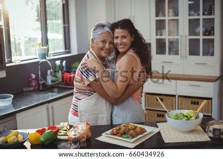 Portrait of mother hugging daughter in kitchen at home