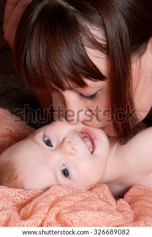 Portrait of mother kissing her baby - stock photo