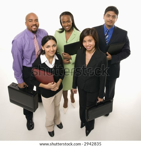 Portrait of multi-ethnic business group standing holding briefcases and looking at viewer. - stock photo