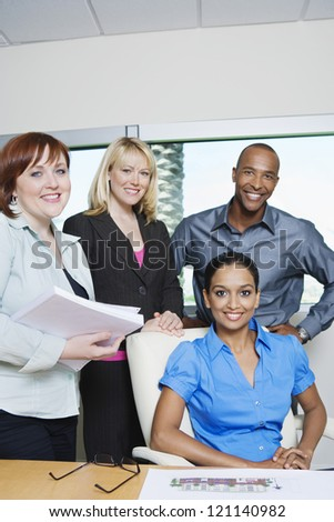 Portrait of multi ethnic business people smiling together in office - stock photo