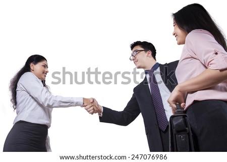 Portrait of multi ethnic business team handshaking, isolated on white background - stock photo