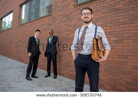 Portrait of multi ethnic business team.Three men standing against the background of city. The foreground of a European man. Other men is Chinese and African-American.  - stock photo
