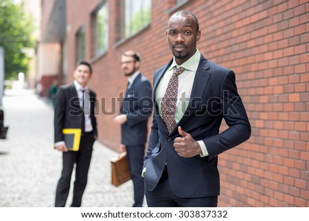 Portrait of multi ethnic business team.Three men standing against the background of red brick wall. The one doubtful man is  African-American. Other men is Chinese and European. the concept of doubt - stock photo