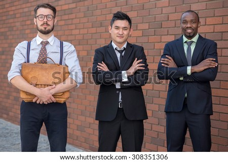 Portrait of multi ethnic business team.Three smiling men standing against the background of red brick wall. The one man is European, other is Chinese and African-American. the concept of old and new - stock photo