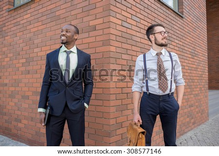 Portrait of multi ethnic business team. Two men standing against the backdrop of the city. The one man is African-American, other is European. concept of business success  - stock photo