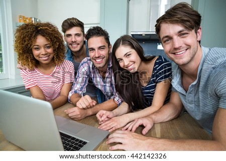 Portrait of multi-ethnic friends smiling while using laptop on table at home - stock photo