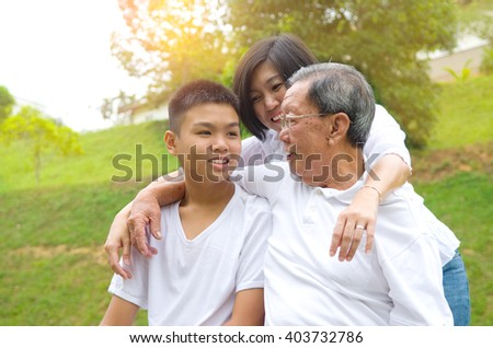 Portrait Of Multi-Generation Chinese Family Relaxing at outdoor Park