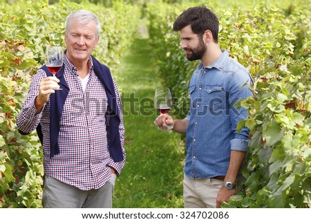 Portrait of multi-generation family working together. Senior winemaker and young professional man standing at vineyard while holding in their hands a glass of wine and tasting it. Small business,