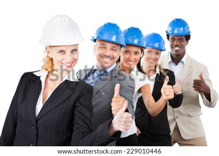 Portrait of multiethnic architects wearing hardhats while gesturing thumbsup against white background - stock photo