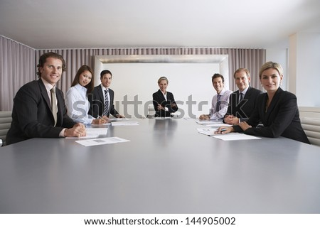 Portrait of multiethnic business people with paperwork in meeting room - stock photo
