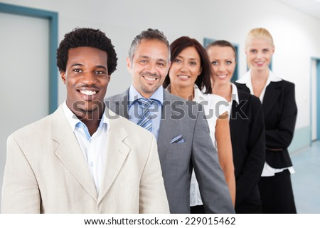 Portrait of multiethnic businesspeople smiling while standing in a row at office - stock photo