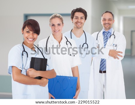 Portrait of multiethnic doctors with stethoscopes around neck standing in hospital - stock photo