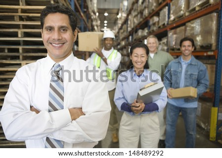 Portrait of multiethnic workers in distribution warehouse - stock photo