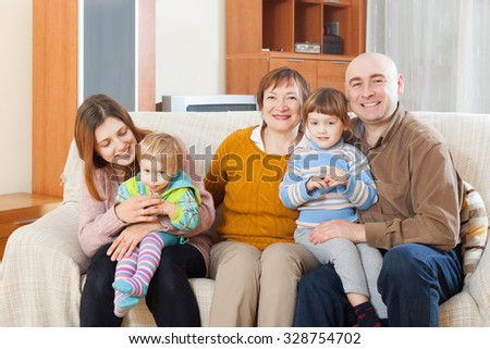 Portrait of multigeneration cheerful family on sofa in home