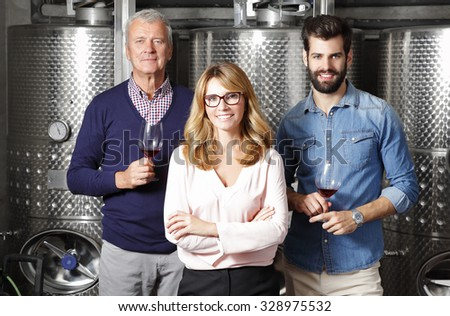 Portrait of multigenerational vinery owner family standing at wine cellar in front of stainless steel vessel and tasting red wine. Small business.  - stock photo