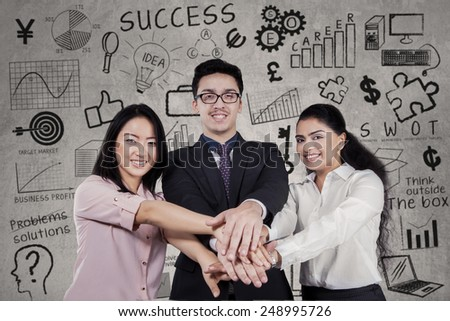 Portrait of multiracial business team joining hands with the scribbles background - stock photo