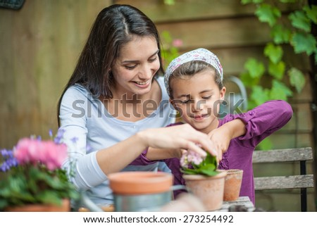Portrait of mumy and her little girl doing gardening - stock photo